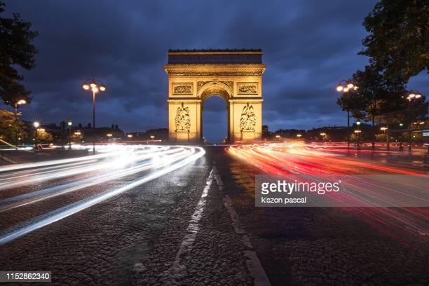 the triumphal arch on etoile place illuminated at night , monument of paris , french culture . - arc de triomphe photos et images de collection
