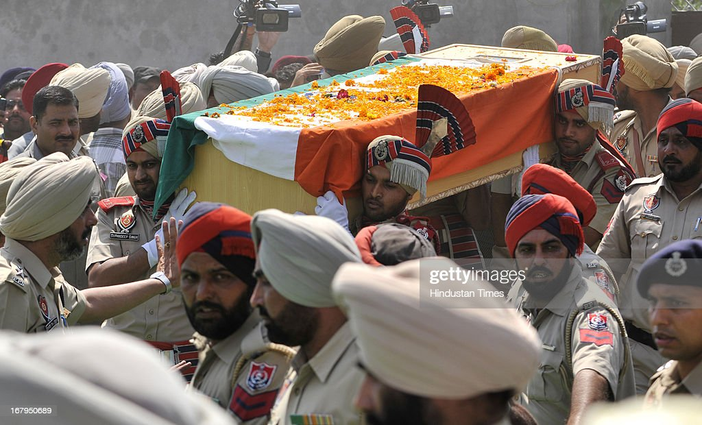 The troops of Punjab Police carries the coffin of Sarabjit Singh during his cremation ceremony at his native village Bikhiwind on May 3, 2013 about 40 Kms from Amritsar, India. Sarabjit Singh, an Indian prisoner in Pakistan who died after being brutally assaulted in a Pakistani jail, was cremated in his native village with full state honours .