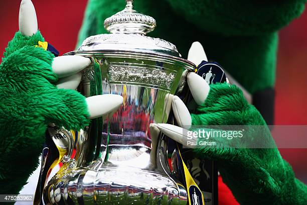 The trophy is carried by mascot Gunnersaurus after the FA Cup Final between Aston Villa and Arsenal at Wembley Stadium on May 30 2015 in London...