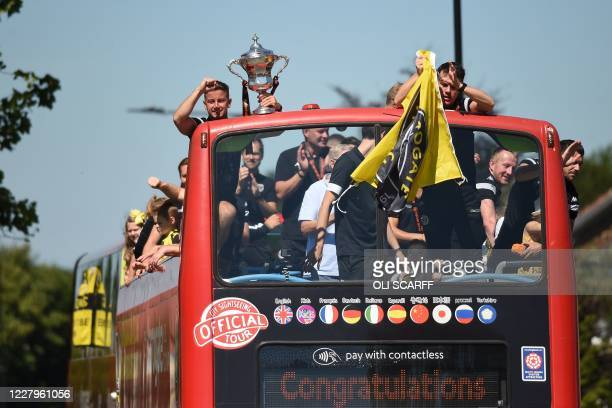 The trophy is held up as Harrogate Town players, families and officials celebrate their promotion to the football league with an open-top bus parade...