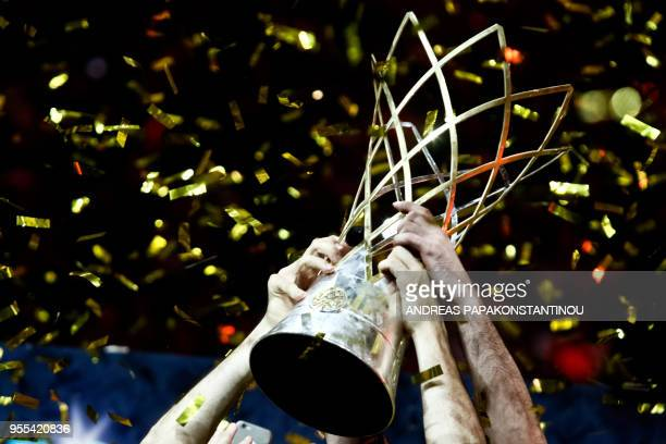 The trophy is pictured as AEK Athens' players celebrate after winning the Final Four Champions League basketball final game between AS Monaco and AEK...