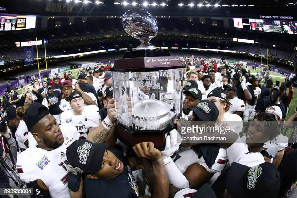 The Troy Trojans celebrate with the trophy after winning the RL Carriers New Orleans Bowl against the North Texas Mean Green at the MercedesBenz...
