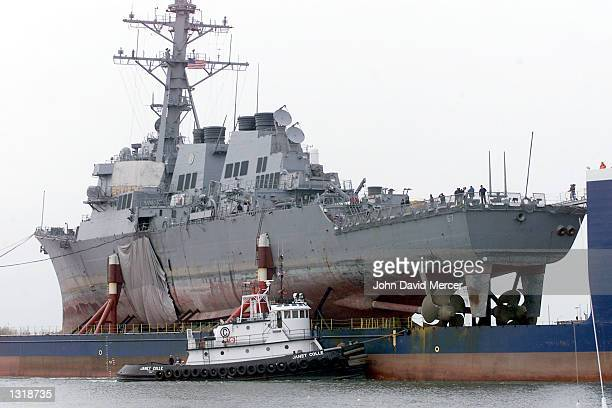 The tugboat Janet Colle assists the USS Cole as it is returned back to the United States December 13 2000 at Ingalls Shipbuilding in Pascagoula MS...