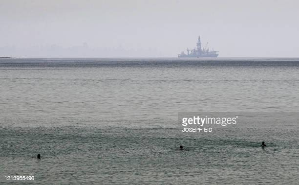 The Tungsten Explorer, an off-shore oil and gas exploration drillship, is seen in the background as people bathe in the Mediterranean water off the...