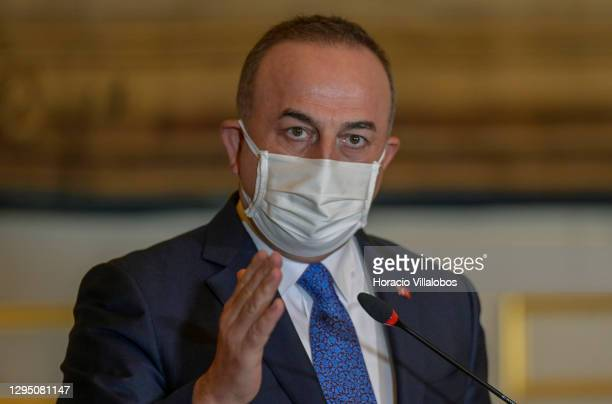 The Turkish Minister of Foreign Affairs Mevlüt Çavuşoğlu wears a protective mask as he delivers remarks during a joint press conference with...