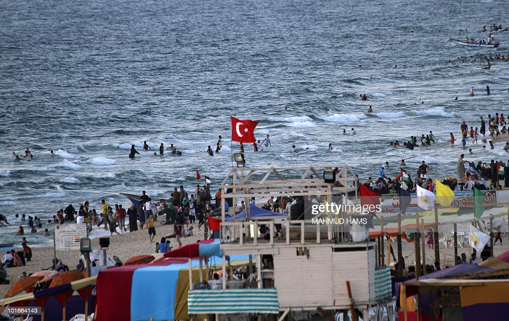 The turkish national flag flutters on a beach hut as Palestinians enjoy the beach in Gaza City on June 06, 2010, a week after several Turkish humanitarian activist riding on an aid flotilla were killed by Israeli commandos as their ship tried to reach the Israeli blockaded Gaza strip.