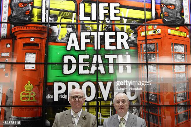 The Turner prize winning duo Gilbert Proesch and George Passmore pose for a photo in front of their art piece during Art Stage Singapore 2015 at...
