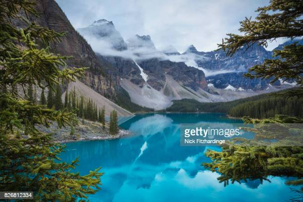 The turquoise Moraine Lake seen through the trees on a foggy day, Banff National Park, Alberta, Canada