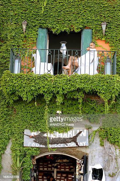 Porto Ercole Secret Paradise Of The Jet Set Façade d'une boutique et vacancier sur son balcon le long du port de Porto Ercole