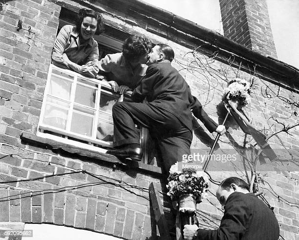 The tutti-men climb a ladder to get the traditional kiss the window during the Hock-tide festival at Hungerford. April 1955 P029159