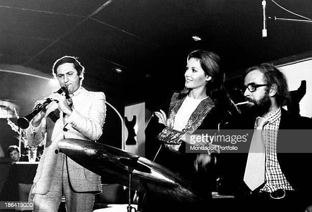 The TV announcer Gabriella Farinon and the musician and journalist Fabrizio Zampa sitting at the drums listen carefully to Renzo Arbore who rehearses...