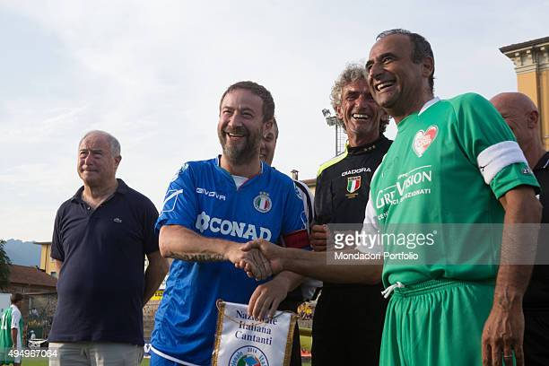 The TV host Carlo Conti and the singersongwriter Marco Masini shaking hands in front of the smiling referee Graziano Cesari during the Partita del...