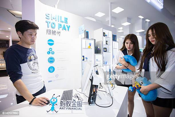 The twin girls experience to pay by facial recognition on the computer at the Ant Financial booth ahead of 2016 The Computing Conference at Yunqi...