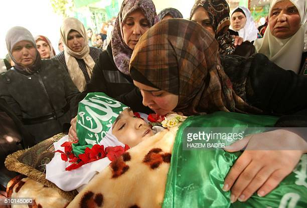 The twin sister of Kalzar alUweiwi a Palestinian teenager who was killed following a reported stabbing attack kisses her body wrapped in the Hamas...