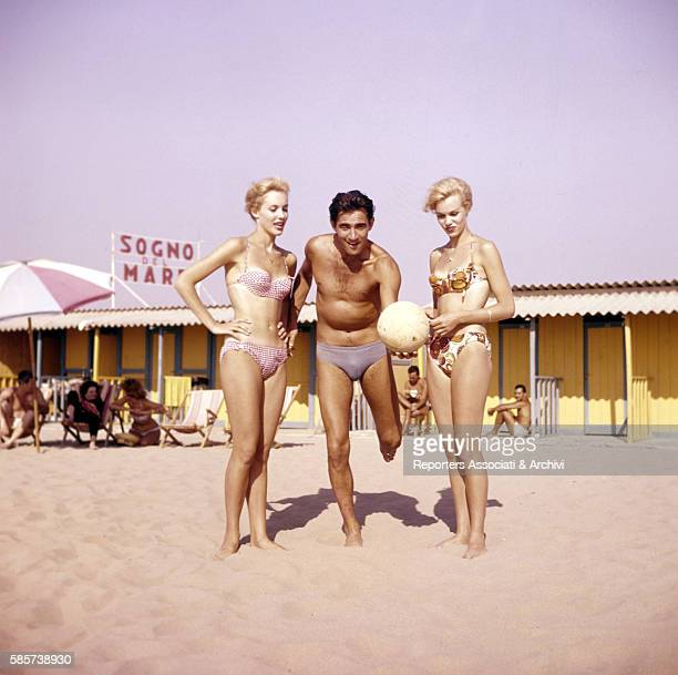 The twin sisters and famous German variety showgirls Alice and Ellen Kessler being photographed at the beach in Fregene while looking at Italian...