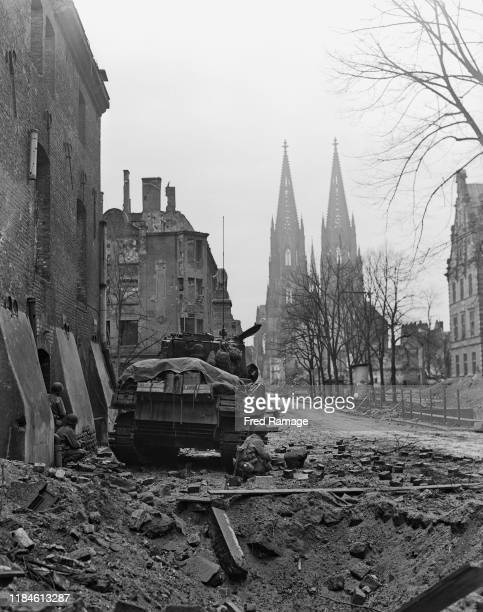 The twin spires of Cologne Cathedral are seen in the background as soldiers of the 3rd Armored Division First Army Corps of the United States advance...