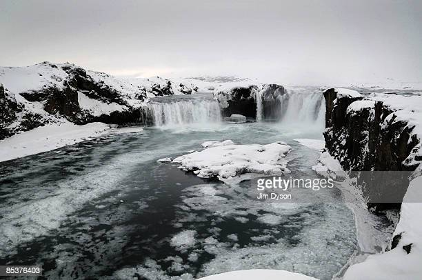 The twin waterfall of Godafoss cascades through the snow covered landscape on February 23, 2009 in north Iceland. A country of glacial and volcanic...