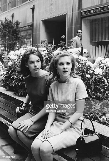 The two daughters of former Vice President Richard Nixon Julie and Tricia sit on a bench and gawk outside the El Al office Rockefeller Center...