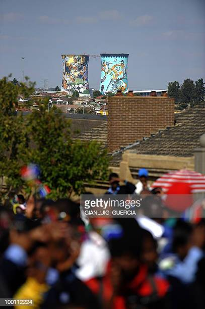 The two decorated Soweto towers are seen in the background as South African children sing and dance on May 21, 2010 during the official celebrations...