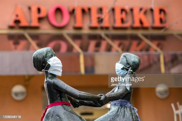 The two female heads of a bronze figure wear a protective face mask on April 3 2020 in Jena Germany A threepart city ordinance is going into effect...