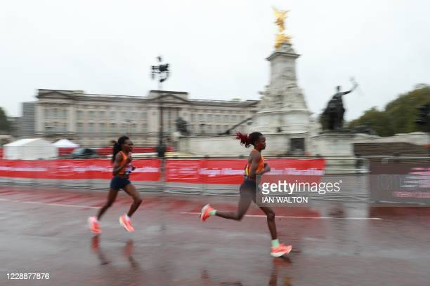 The two leaders Kenya's Ruth Chepngetich and Kenya's Brigid Kosgei run past the Victoria Memorial in front of Buckingham Palace during the women's...