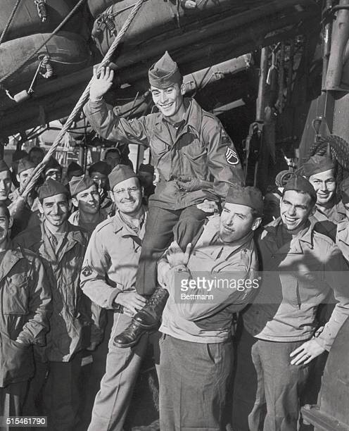 The two millionth serviceman to return from the Pacific Sgt Irving Feldman of Worcester Mass is carried on the shoulders of his buddies Jake G...
