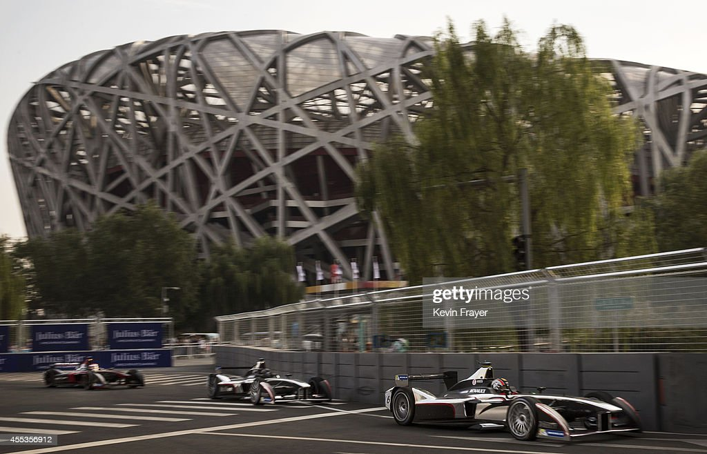 The two team cars of Dragon racing pass the Birds Nest Olympic Stadium during the FIA Formula E Beijing ePrix Championship on September 13, 2014 in Beijing, China. The electric car racing series is backed by many of the major sponsors of the main Formula One circuit and is set to be hosted in nine other cities worldwide.