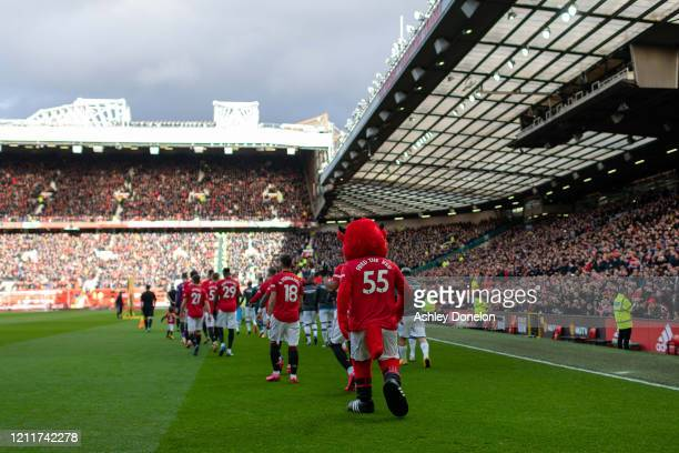 The two team walk out ahead of the Premier League match between Manchester United and Manchester City at Old Trafford on March 08 2020 in Manchester...