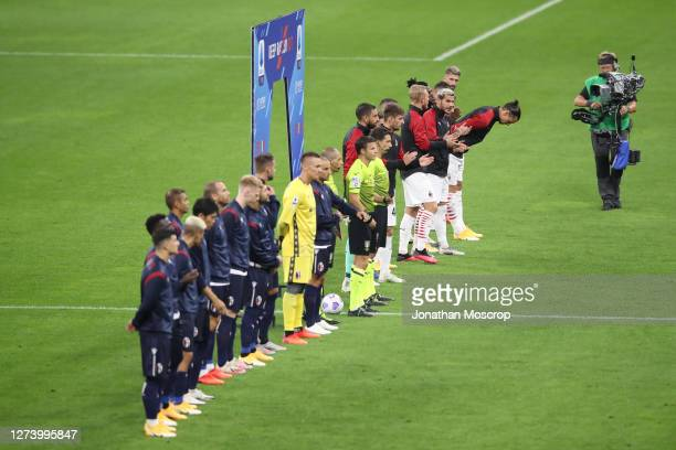 The two teams and officials line up before kick off for the Serie A match between AC Milan and Bologna FC at Stadio Giuseppe Meazza on September 21...