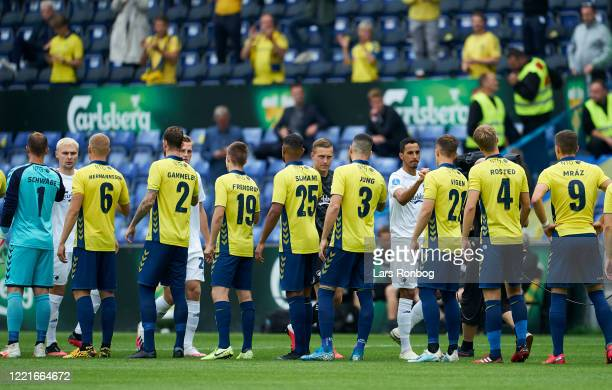 The two teams greeting each other prior to the Danish 3F Superliga match between Brondby IF and FC Copenhagen at Brondby Stadion on June 21, 2020 in...