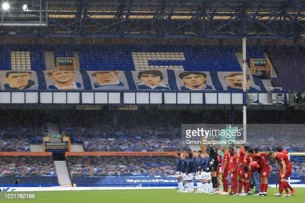 The two teams line up in front of empty seats at before the Premier League match between Everton FC and Liverpool FC at Goodison Park on June 21,...