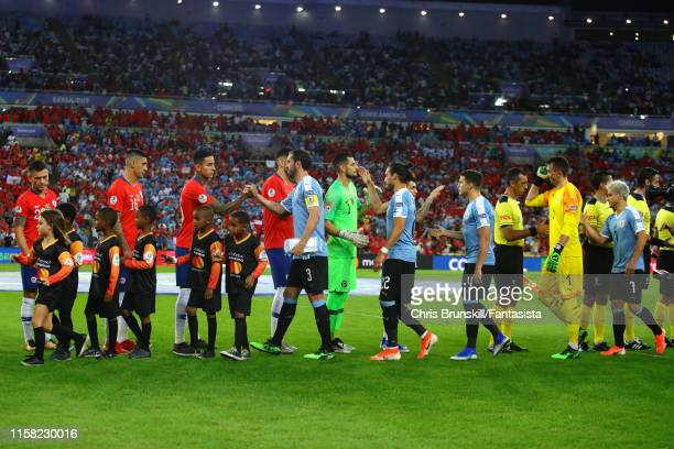 The two teams shake hands ahead of the Copa America Brazil 2019 group C match between Chile and Uruguay at Maracana Stadium on June 24 2019 in Rio de...