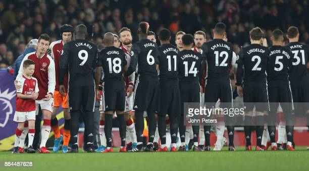 The two teams shake hands ahead of the Premier League match between Arsenal and Manchester United at Emirates Stadium on December 2 2017 in London...