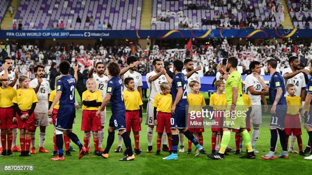 The two teams shake hands prior to the FIFA Club World Cup UAE 2017 play off match between Al Jazira and Auckland City FC at on December 6 2017 in Al...