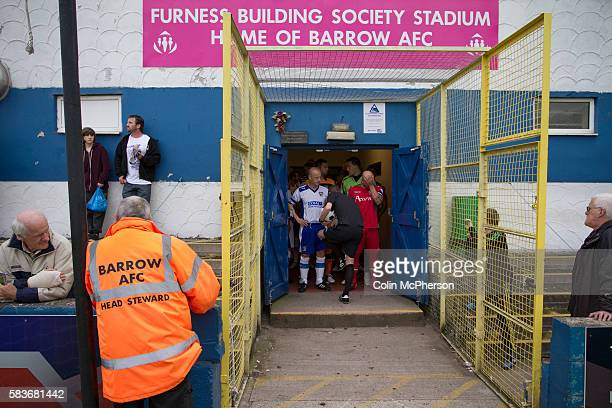 The two teams standing in the tunnel with the referee at Barrow AFC's Furness Building Society Stadium prior to the delayed kick-off of the Barrow v...
