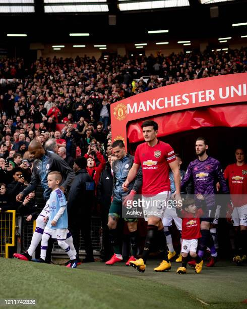 The two teams walk out ahead of the Premier League match between Manchester United and Manchester City at Old Trafford on March 08 2020 in Manchester...