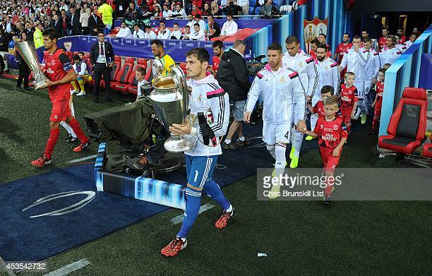 The two teams walk out ahead of the UEFA Super Cup match between Real Madrid and Sevilla FC at Cardiff City Stadium on August 12 2014 in Cardiff Wales