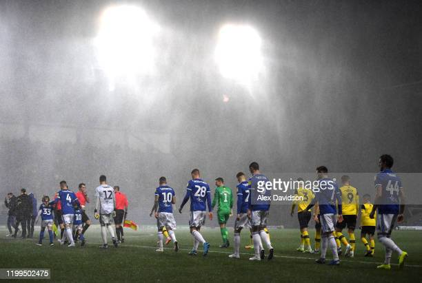 The two teams walk out as rain pours prior to the Sky Bet Leauge One match between Oxford United and Ipswich Town at Kassam Stadium on January 14...
