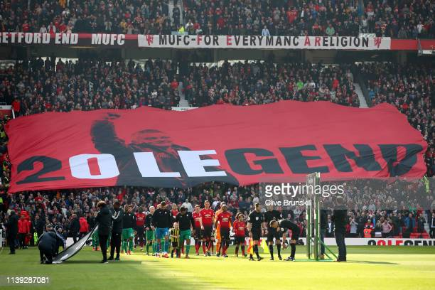 The two teams walk out as the Manchester United fans hold up a banner for Ole Gunnar Solskjaer Manager of Manchester United prior to the Premier...