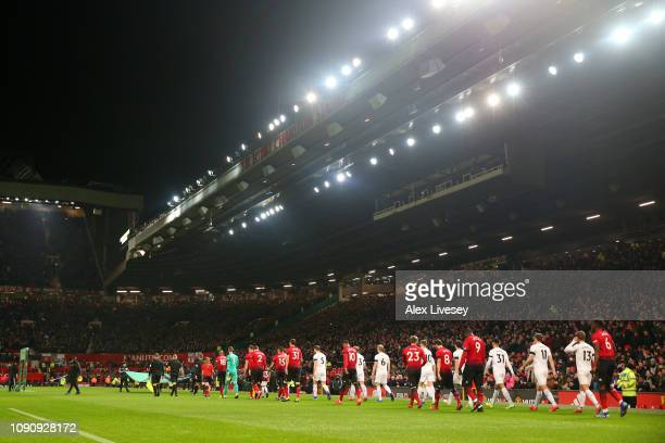 The two teams walk out prior to the Premier League match between Manchester United and Burnley at Old Trafford on January 29 2019 in Manchester...