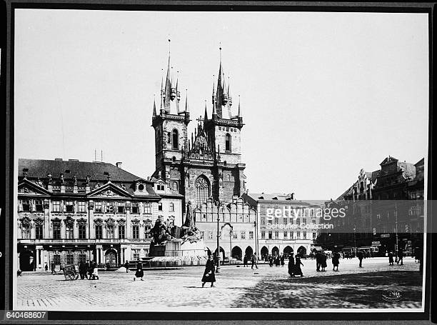 The two towers of the Church of Our Lady Before Tyn rise above the Kinsky Palace and the Hus monument People stroll across the Old Town Square