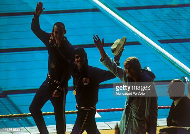 The two US swimmers Mark Spitz and Steve Genter and the German Werner Lampe greet the public after having received the medals of the final of 200...