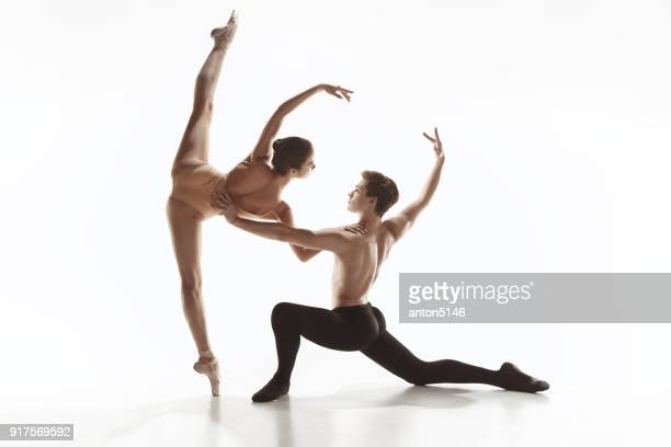 the two young modern ballet dancers posing over gray studio background - male ballet dancer stock photos and pictures