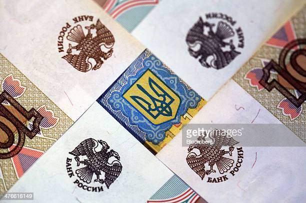 The twoheaded eagle symbol of Russia's central bank sits on ruble banknotes surrounding the Ukraine coat of arms symbol on a Ukrainian hryvnia...