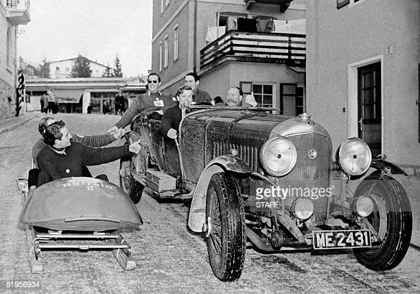 The twoman bobsleigh team from Great Britain greets passengers riding in a Bentley 25 February 1956 in the streets of Cortina d'Ampezzo on the eve of...