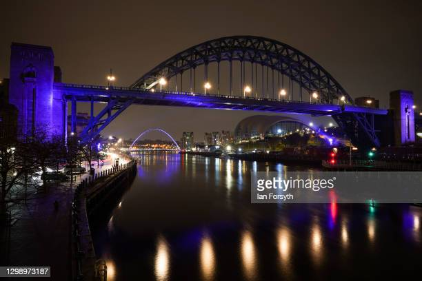 The Tyne Bridge and beyond it the Millennium Bridge in Newcastle are bathed in purple light to commemorate Holocaust Memorial Day on January 27, 2021...
