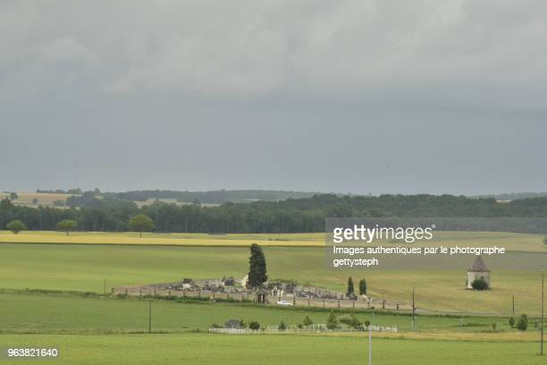 The typical cemetery and abandoned pigeonhole in middle rural landscape under gray sky