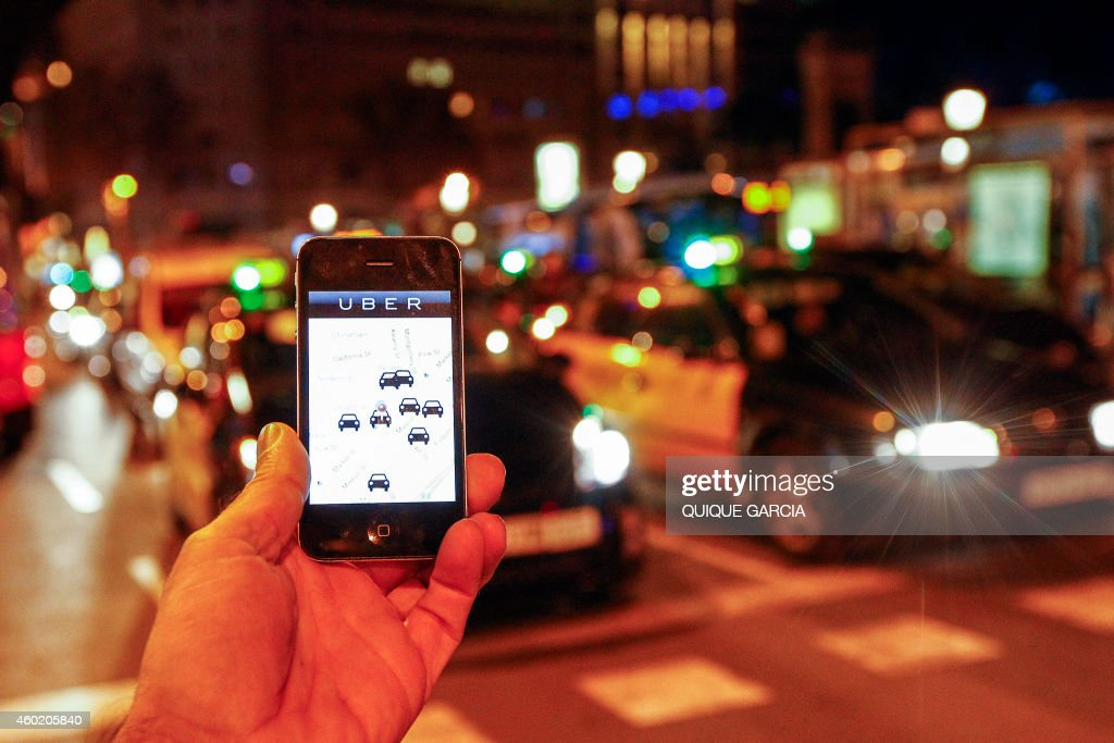 The Uber app is seen on a smartphone past cabs passing on Paseo de Gracia in Barcelona, on December 9, 2014. A judge on December 9, 2014 banned the popular smartphone taxi service Uber from operating in Spain, court officials said, following similar prohibition action in several other countries.