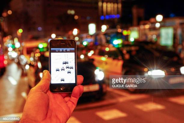 The Uber app is seen on a smartphone past cabs passing on Paseo de Gracia in Barcelona on December 9 2014 A judge on December 9 2014 banned the...