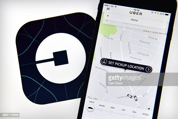 The Uber home page is displayed on an iPhone next to the company logo on a computer screen on August 3 2016 in London England